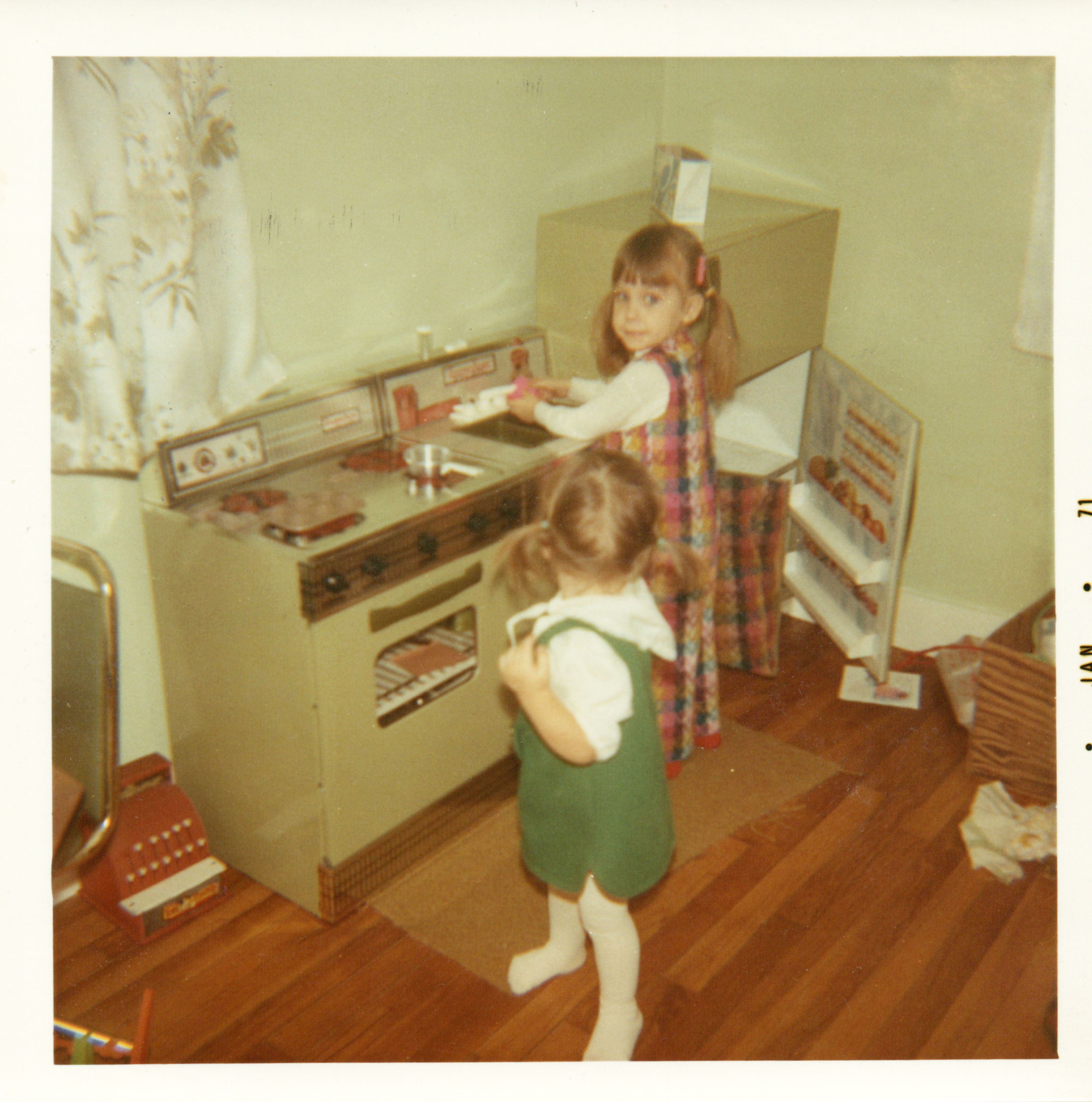 A photo of Two young girls pretending to be moms in a play kitchen