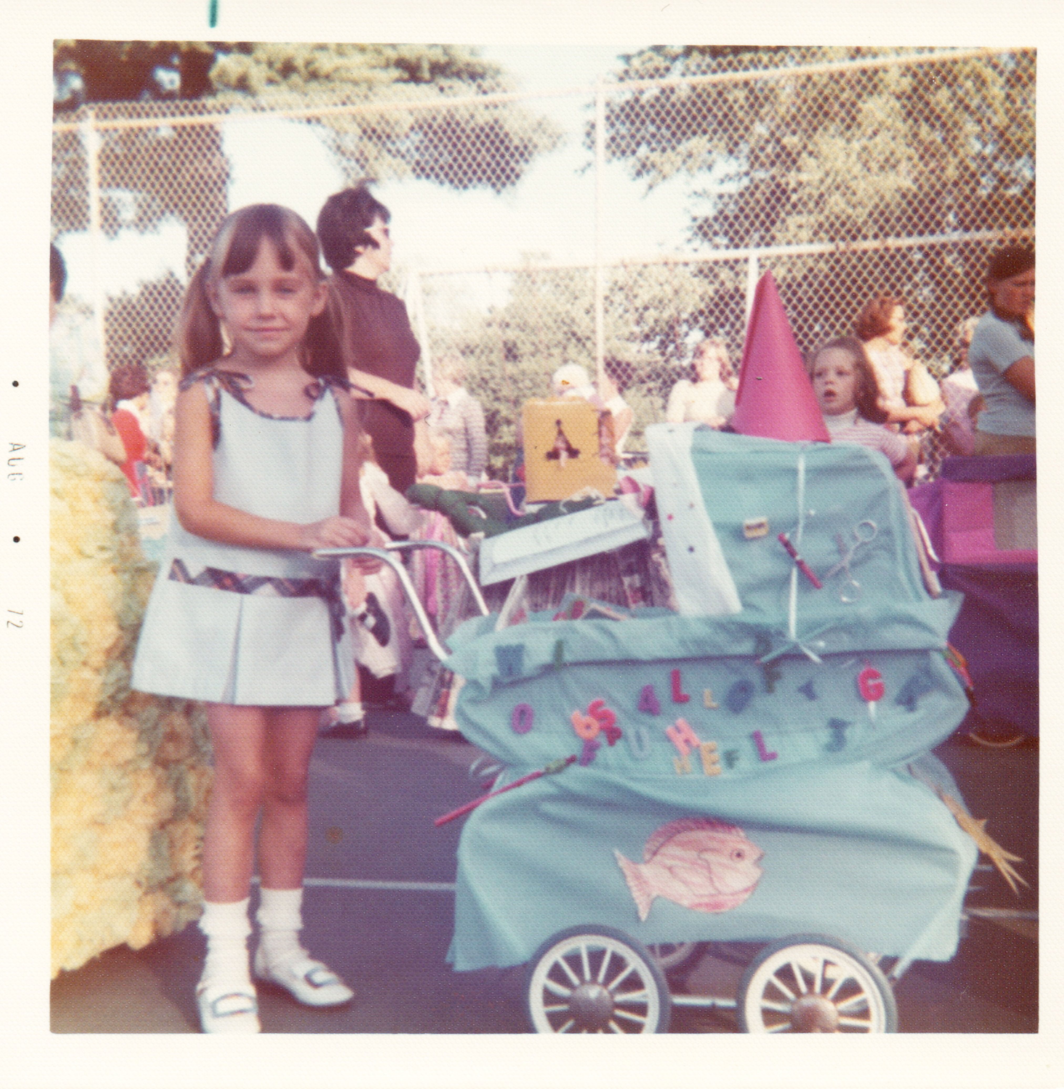 A photo of a girl with a decorated doll carriage.