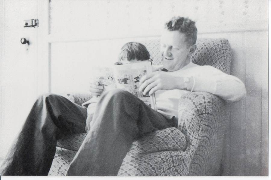 Photo of a girl with her uncle reading a book
