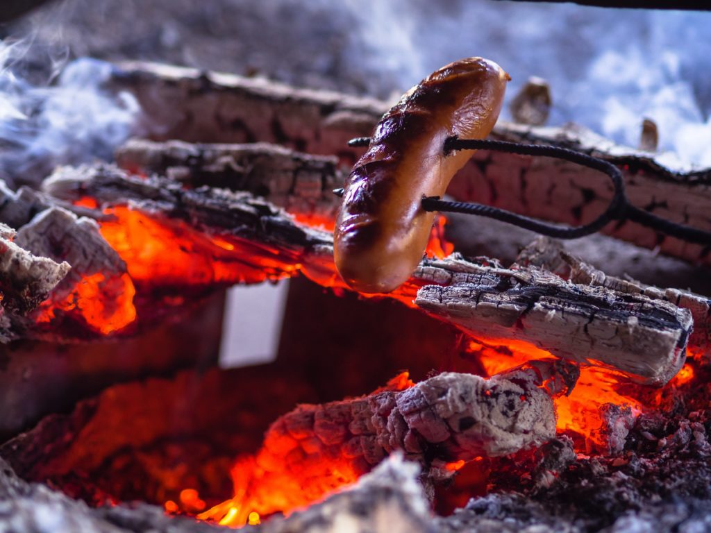 Photo of hot dogs roasting over an open fire