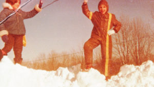 How to enjoy a snow storm New England style. A photo of two girls on top of a 15-foot snow bank.