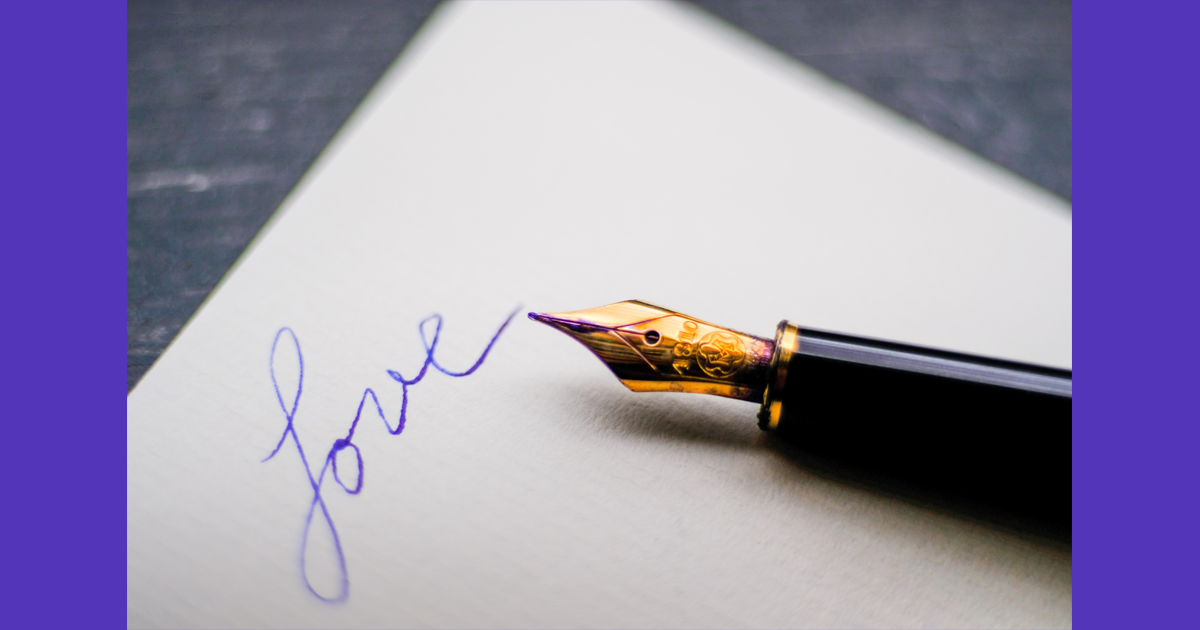 The power of the pen writing the word Love in purple ink.